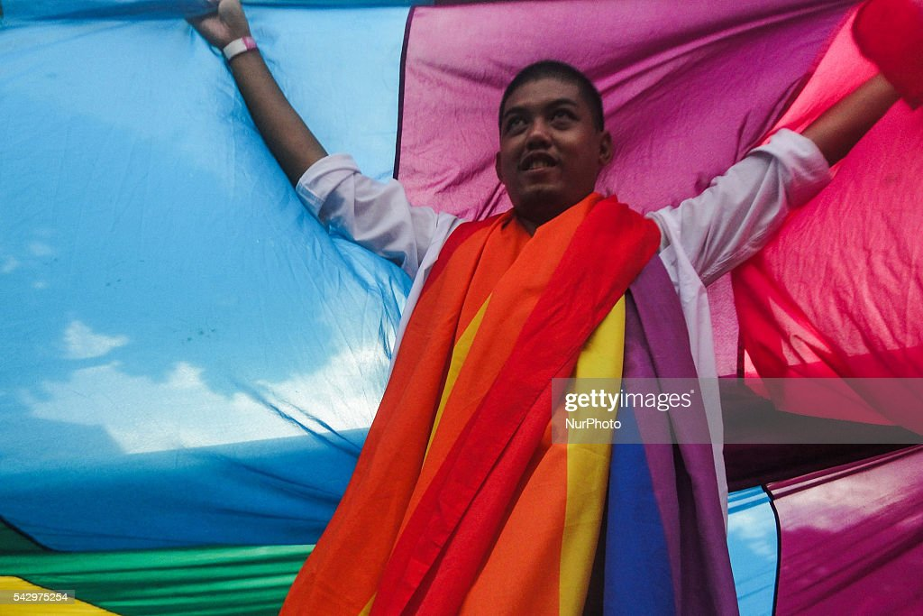 A member of the LGBT community holds a giant rainbow flag as he leads the march during a LGBT pride event at Rizal Park in Manila on Saturday, 25 June 2016. Hundreds of supporters and members of the lesbian, gay, bisexual, and transgender (LGBT) community paraded in Manila calling for the passage of an anti-discrimination law, as well as calling for justice for the shooting in a gay club in Orlando that left 53 people dead.