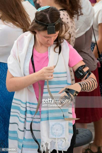 A member of the liberal Jewish religious group Women of the Wall wears phylacteries and a traditional Jewish prayer shawl for men known as 'Tallit'...