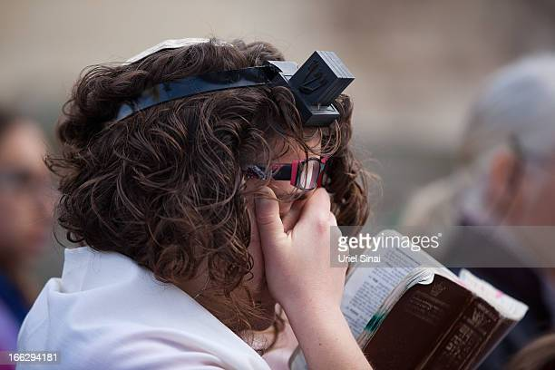 A member of the liberal religious group 'Women of the Wall' wearing phylacteries and a 'Tallit' prays at the Western Wall on April 11 2013 in...