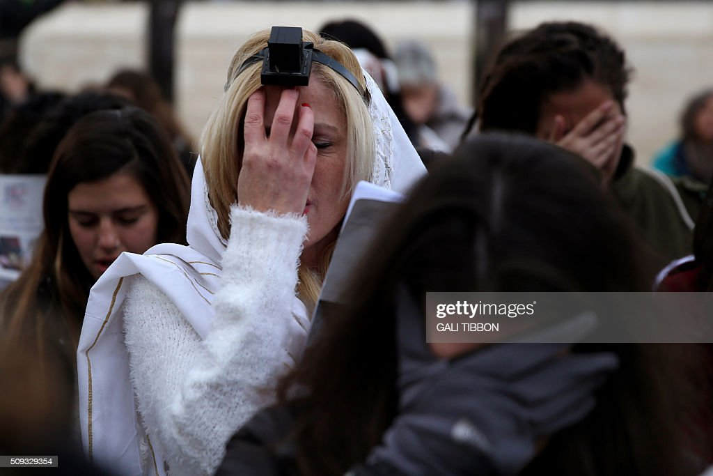 A member of the liberal religious group 'Women of the Wall' wears phylacteries and a 'Tallit' shawl, traditional Jewish prayer apparel for men, as she prays with fellow female worshipers at the Western Wall in Jerusalems Old City on February 10, 2016 marking Rosh Hodesh Adar (the first day of the Jewish month). / AFP / GALI TIBBON