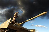 A member of the Libyan army stands on a tank as heavy black smoke rises from the city's port in the background after a fire broke out at a car tyre...