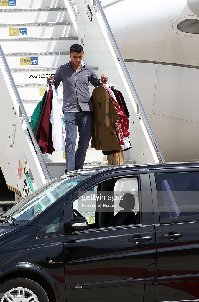A member of the Libyan leader Muammar Gaddafi entourage, carries clothes at the Ciampino airport on August 29, 2010 in Rome, Italy. Gadaffi is on an official two-day visit to Italy for talks with Prime Minister Silvio Berlusconi. The visit also marks the second anniversary of a friendship treaty between Italy and Lybia.