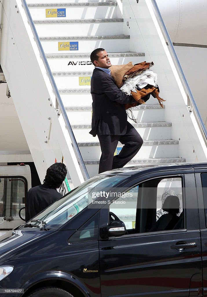 A member of the Libyan leader Muammar Gaddafi's entourage, carries clothes at Ciampino airport on August 29, 2010 in Rome, Italy. Gadaffi is on an official two-day visit to Italy for talks with Prime Minister Silvio Berlusconi. The visit also marks the second anniversary of a friendship treaty between Italy and Lybia.