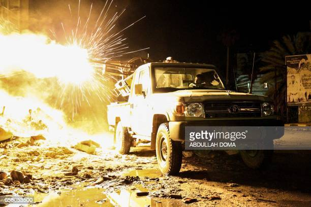 TOPSHOT A member of the Libyan National Army fires a machine gun mounted on the back of a Toyota pickup truck against jihadists in district of Suq...