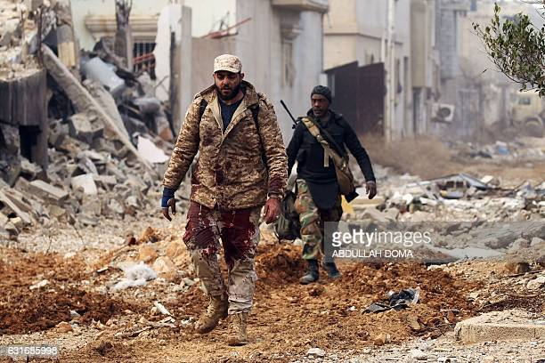 A member of the Libyan National Army has his pants covered with blood after carrying an injured comrade during fighting against jihadists in Qanfudah...