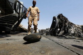 A member of the Libyan security forces inspects the destruction at Tripoli international airport in the Libyan capital on July 21 2014 after...