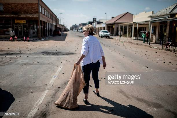 TOPSHOT A member of the local Afrikaner community in Coligny takes part in a clean up on April 26 2017 The shops on the main street of the North...
