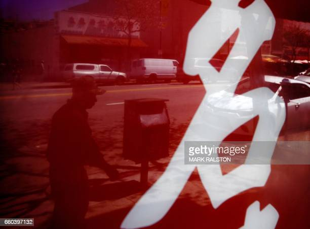 TOPSHOT A member of the local Asian community walks on the streets of Chinatown in Los Angeles California on March 29 2017 Of the estimated 11...