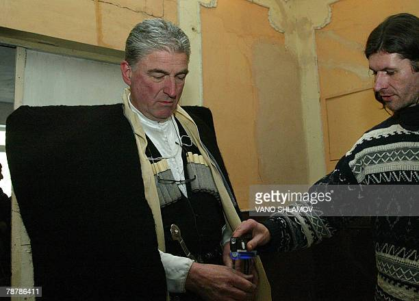 A member of the local electoral commission checks the fingers of a Georgian man dressed in a traditional felt cloak at a polling station in Tbilisi...