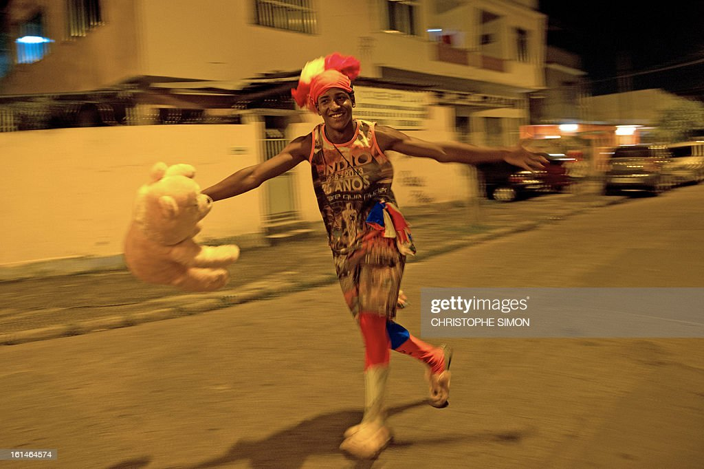 A member of the local 'Indio' carnival group of the Guadalupe neighborhood in northern Rio de Janeiro, Brazil, takes part in their 'Bate Bola' traditional parade on February 10, 2013. AFP PHOTO/Christophe Simon