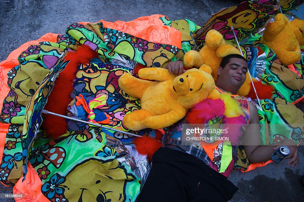 A member of the local 'Indio' carnival group of the Guadalupe neighborhood in northern Rio de Janeiro, Brazil, takes a rest before participating in their 'Bate Bola' traditional parade on February 10, 2013. AFP PHOTO/Christophe Simon