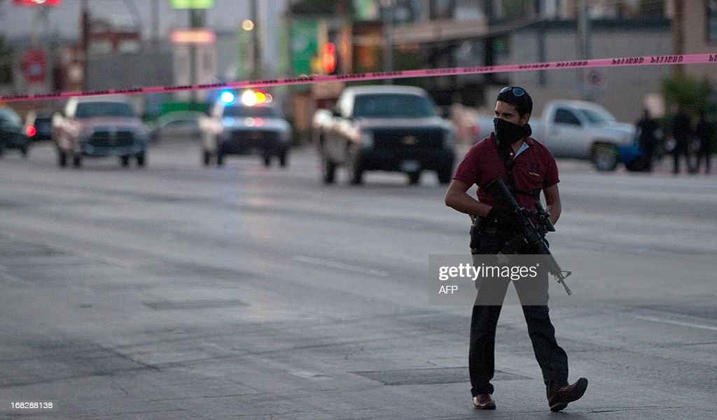 A member of the local police in plain clothes patrols the avenue near an exclusive restaurant in Ciudad Juarez Chihuahua state Mexico on May 07 after...