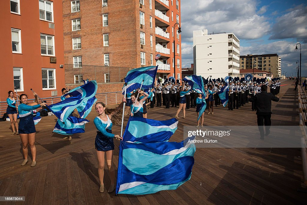 A member of the Long Beach High School color guard waves her flag while marching down the Long Beach boardwalk during a ceremony to officially reopen the boardwalk on October 25, 2013 in Long Beach, New York. The boardwalk was severely damaged by Superstorm Sandy last year, which killed 285 people and caused billions of dollars in damage. Long Beach's new boardwalk is made of Brazilian hardwood and is estimated to have a lifespan of 30-40 year; the previous boardwalk was only scheduled to last three to seven years.