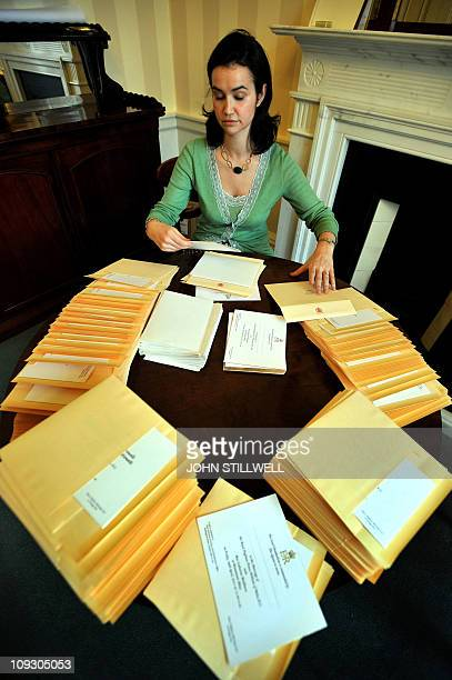 GMTA member of the Lord Chamberlain's Office at Buckingham Palace in London inserts on February 16 2011 the invitations of Prince William and Kate...