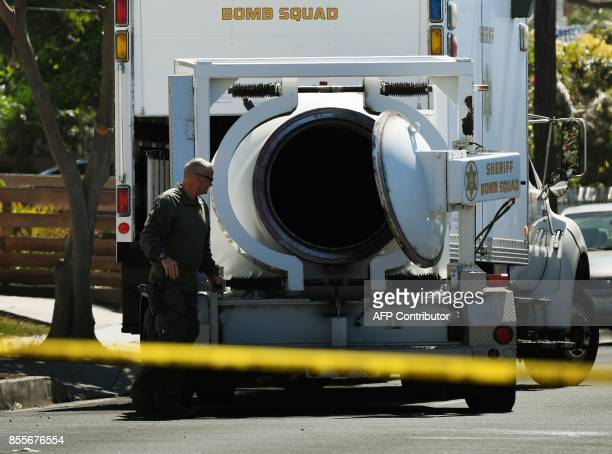 A member of the Los Angeles County Sheriff's Department bomb and hazmat squad checks the contents of a bombproof container beside a house where a...
