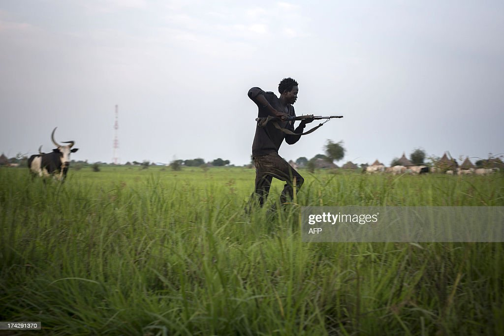A member of the Lou Nuer tribe comes back home in the Yuai village, Uror county, Jonglei state in South Sudan, on July 23, 2013 after fighting against the rebel group of Yau Yau in Pibor county, South Sudan. Over 100,000 South Sudanese civilians are cut off from aid in the eastern state of Jonglei amid fierce fighting between rival ethnic groups, aid agencies and the United Nations warned on July 17. AFP PHOTO / CAMILLE LEPAGE