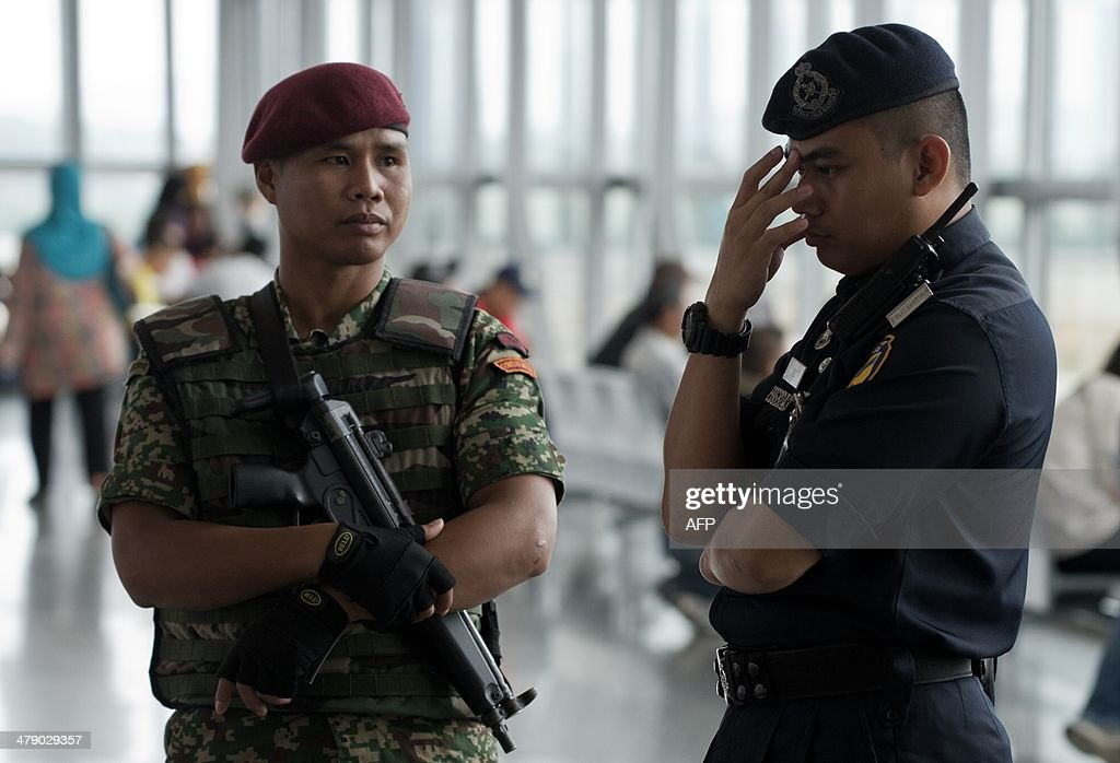 A member of the Malaysian Army (L) and a Malaysian policeman (R) stand guard at Kuala Lumpur International Airport (KLIA) in Sepang, outside Kuala Lumpur on March 16, 2014. Malaysia said on March 16 that police had searched the homes of the pilots of the missing jet and examined a home flight simulator after revelations that the flight was deliberately diverted triggered a full-scale criminal probe.