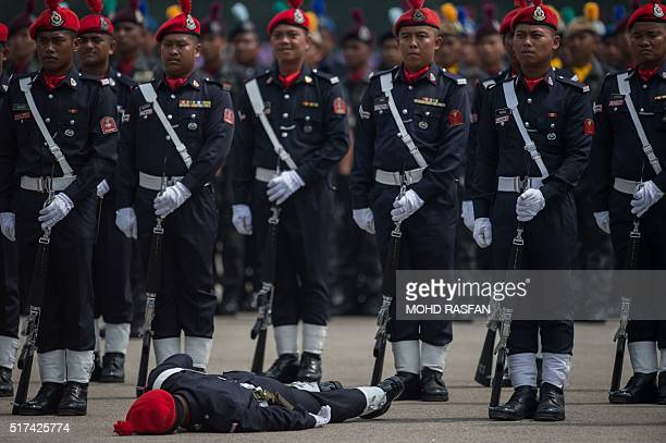 TOPSHOT A member of the Malaysia's Federal Reserve Unit lies on the ground after fainting due to the hot weather during the 209th Police Day parade...