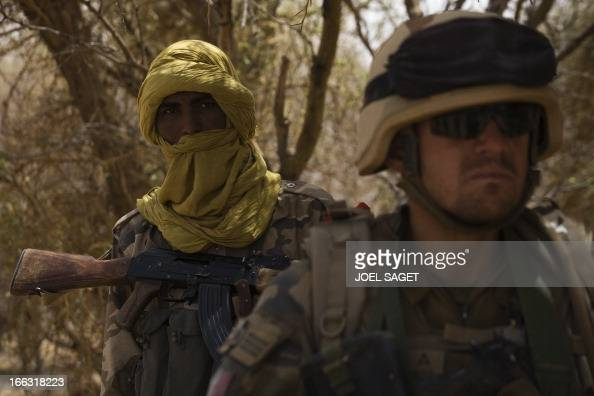 A member of the Malian special forces and a French soldier take part on April 10 105 kms north of the northeastern Malian city of Gao in day three of...