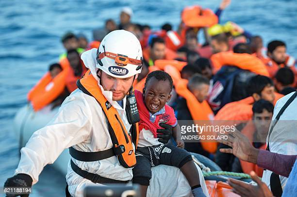 A member of the Maltese NGO MOAS helps a baby to board a small rescue boat during a rescue operation of 146 migrants and refugees by the Topaz...