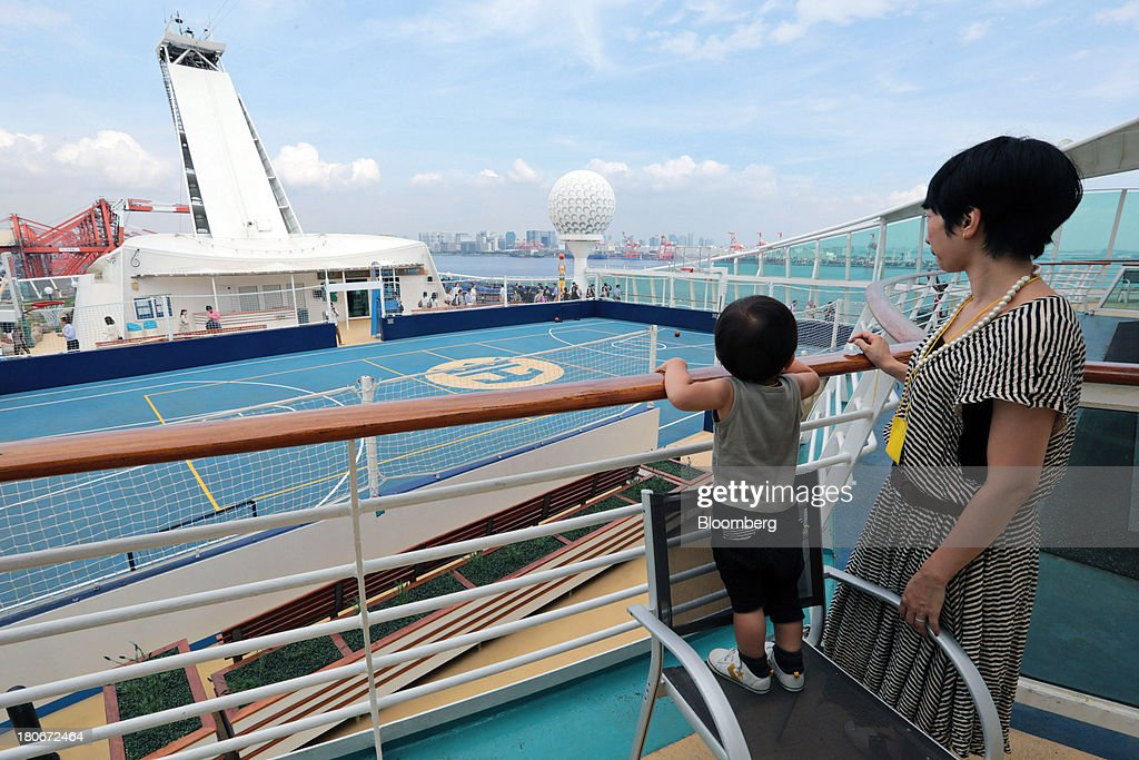 A member of the media and her son look out towards the sports court during a tour of the Royal Caribbean Cruises Ltd.'s Voyager of the Seas, berthed at the Ohi wharf in Tokyo, Japan, on Saturday, Sept. 14, 2013. Royal Caribbean, the worlds second-largest cruise-line operator, doubled its dividend and will make directors stand for election every year. Photographer: Yuriko Nakao/Bloomber