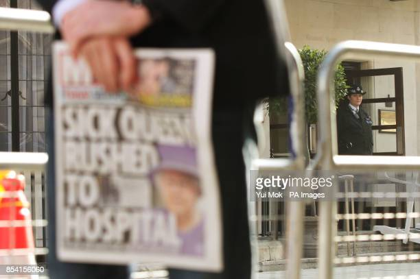 A member of the media holding a newspaper outside the King Edward VII Hospital in London where Queen Elizabeth II is continuing her recovery after...