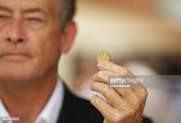 A member of the media holds aloft a AUD$1 coin during the home auction for a fourbedroom house at 230 Blacktown Road on February 14 2015 in Blacktown...