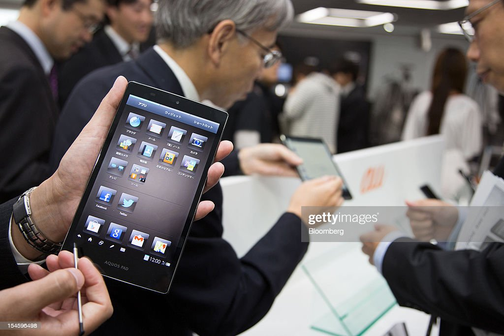 A member of the media holds up Sharp Corp.'s AQUOS Pad SHT21 tablet device that features the new IGZO display in Tokyo, Japan, on Tuesday, Oct. 23, 2012. Sharp began making smartphone displays using a semiconductor technology known as IGZO this month at its plant in Tenri, central Japan, according to a company spokesman. Photographer: Noriyuki Aida/Bloomberg via Getty Images