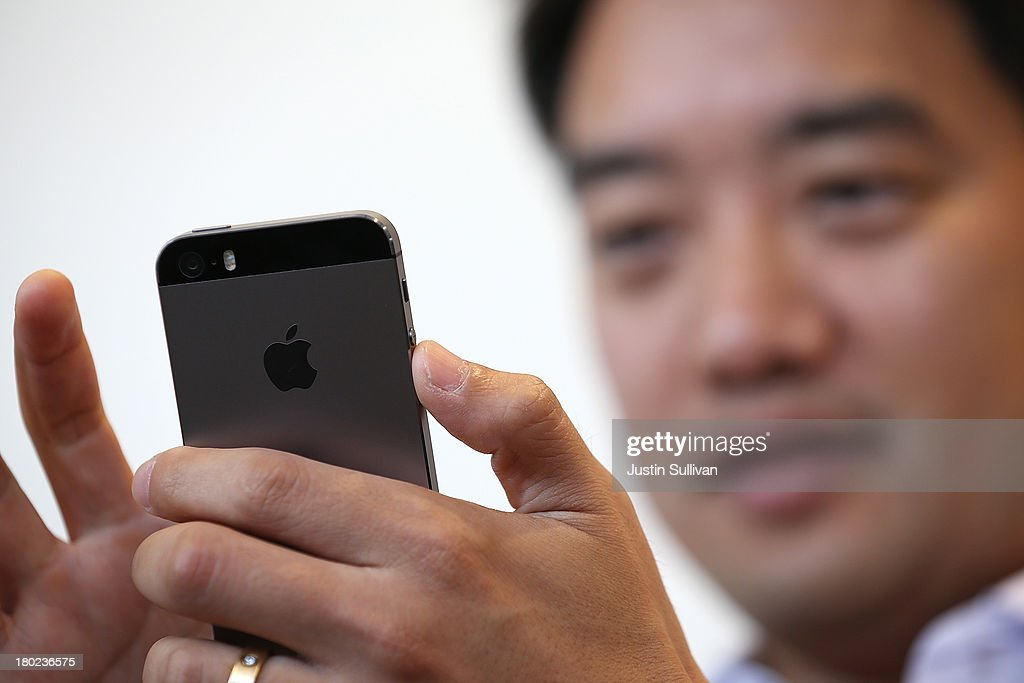 A member of the media inspects the new iPhone 5S during an Apple product announcement at the Apple campus on September 10, 2013 in Cupertino, California. The company launched the new iPhone 5C model that will run iOS 7 is made from hard-coated polycarbonate and comes in various colors and the iPhone 5S that features fingerprint recognition security.