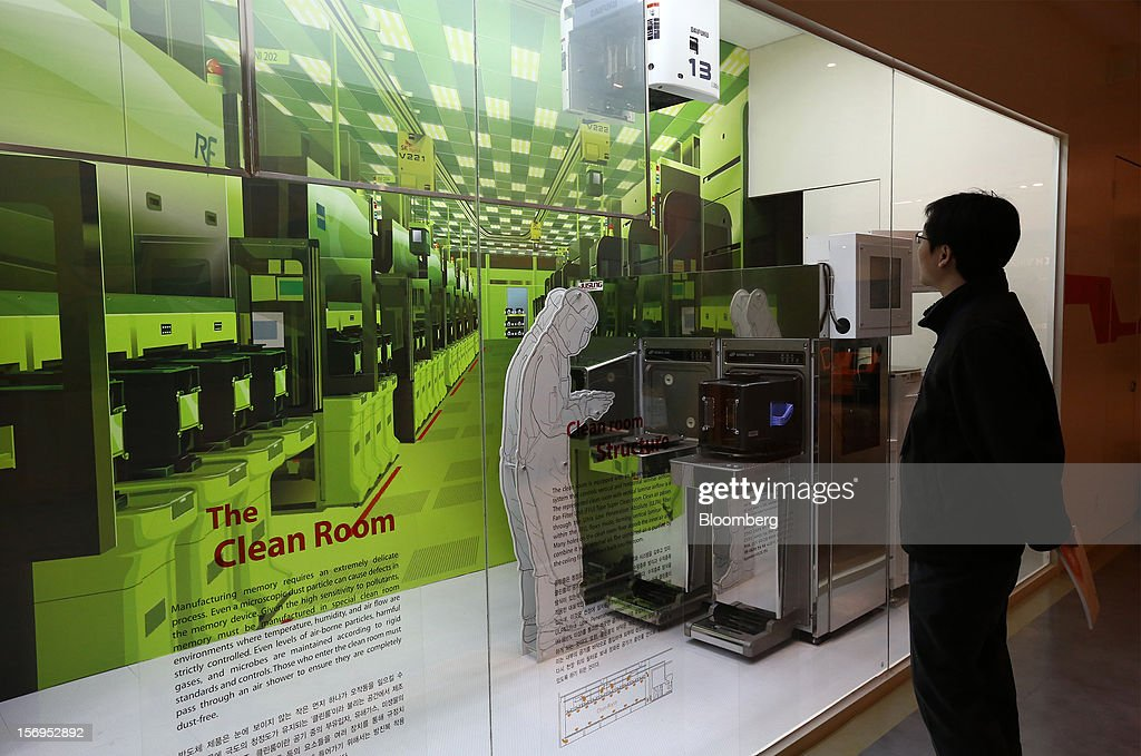 A member of the media looks at a display showing the clean room in the show room of the SK Hynix Semiconductor Inc. plant during a media tour organized by Korea Industrial Complex Corp. (KICOX) in Cheongju, South Korea, on Friday, Nov. 23, 2012. KICOX, which develops and manages industrial complexes and support for resident enterprises as a public company under South Korea's Ministry of Knowledge Economy, held a media tour to the plant. Photographer: SeongJoon Cho/Bloomberg via Getty Images