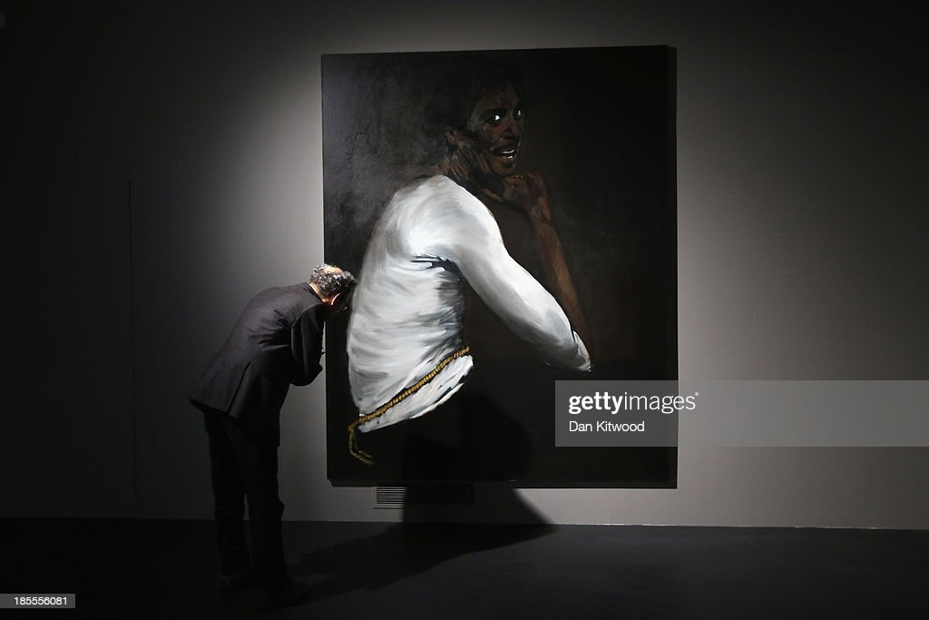 A member of the media looks at a painting by Turner Prize nominated artist Lynette Yiadom-Boakye in Building 80/81, a former Army base in Ebrington Square on October 22, 2013 in Londonderry, Northern Ireland. This year the Turner Prize which is in it's 29th year is held in Londonderry, Northern Ireland, which is the first time it has left England. The winner will be announced on December 2, 2013.