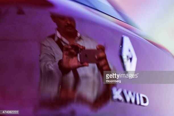 A member of the media photographing the Renault SA Kwid compact is reflected in the vehicle during a launch event in Chennai India on Wednesday May...
