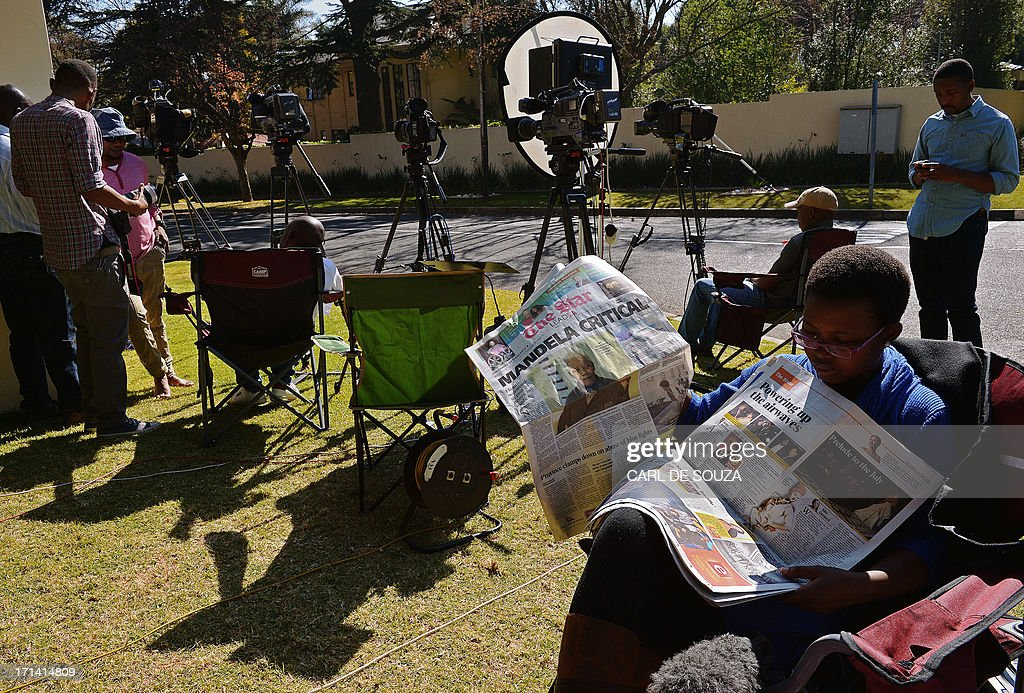 A member of the media reads a newspaper whose front page carries headlines of Nelson Mandela being in a critical condition as she sits outside the home of former South African President Nelson Mandela in Johannesburg on June 24, 2013. Anti-apartheid icon Nelson Mandela remained in a critical condition in hospital today, leaving millions in South Africa and across the world fearing the worst. Mandela, the hero of black South Africans' battle for freedom during 27 years in apartheid jails, was rushed to hospital on June 8 with a recurrent lung infection. AFP PHOTO/Carl de Souza