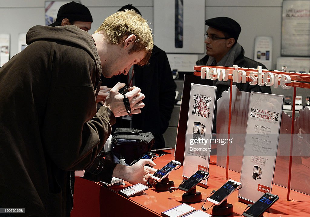 "A member of the media shoots video of a new Blackberry Z10 device displayed on the first day of sales at a Rogers Communications Inc. store in Toronto, Ontario, Canada, on Tuesday, Feb. 5, 2013. Thorsten Heins, president and chief executive officer of BlackBerry, said early sales of the Z10 smartphone are ""encouraging"" and that users are switching from other platforms. Photographer: Aaron Harris/Bloomberg via Getty Images"
