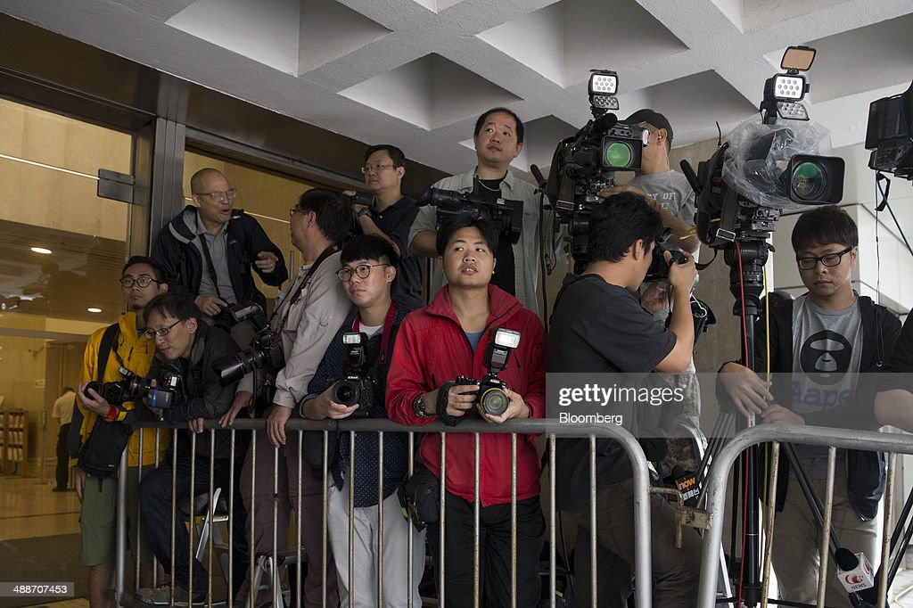 Member of the media stand waiting at the entrance to the High Court in Hong Kong, China, on Thursday, May 8, 2014. Thomas and Raymond Kwok, the billionaire brothers running Hong Kongs second-largest developer, are set to go on trial today for bribing Rafael Hui, the Chinese citys former No. 2 official. All three men have pleaded not guilty and denied all charges. Photographer: Brent Lewin/Bloomberg via Getty Images