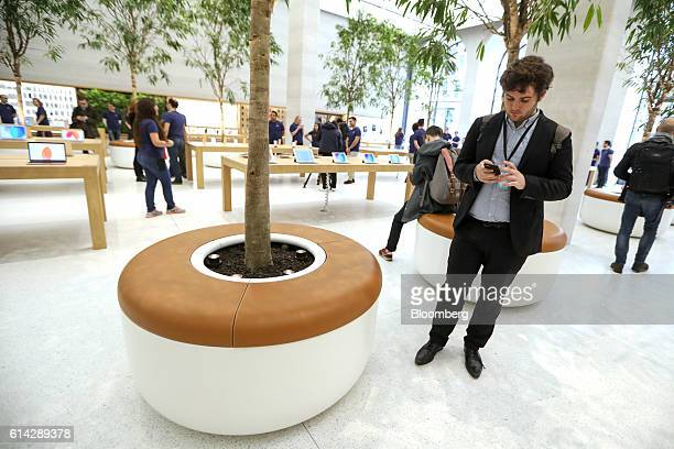A member of the media stands next to one of 12 Ficus Ali trees inside the newly refurbished Apple Inc store on Regent Street in London UK on Thursday...