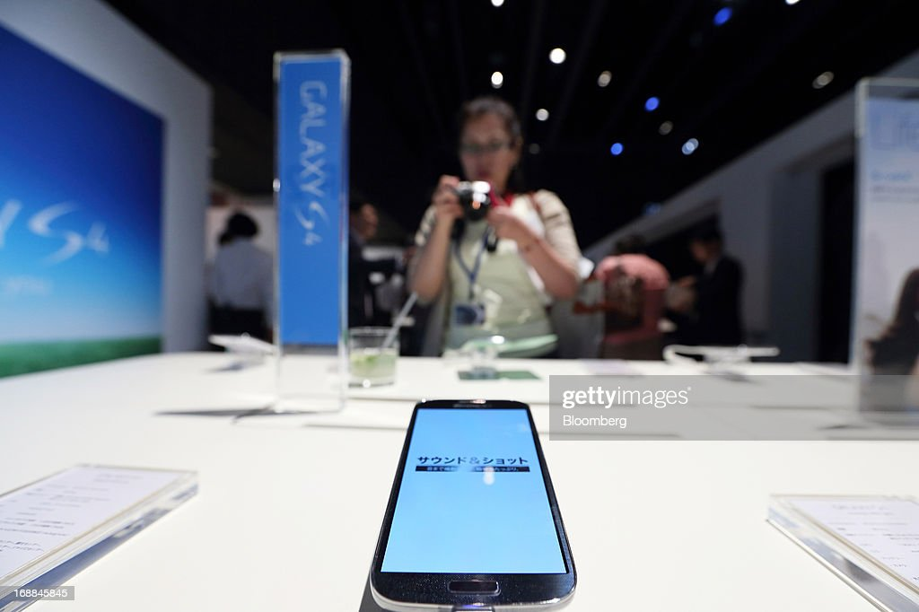 A member of the media takes a photograph of a Samsung Electronics Co. Galaxy S4 smartphone for NTT DoCoMo Inc. displayed during the Galaxy S4 World Tour 2013 Tokyo event in Tokyo, Japan, on Thursday, May 16, 2013. Samsung Electronics reported a record quarterly profit in April for the three months ended March 31. Photographer: Tomohiro Ohsumi/Bloomberg via Getty Images