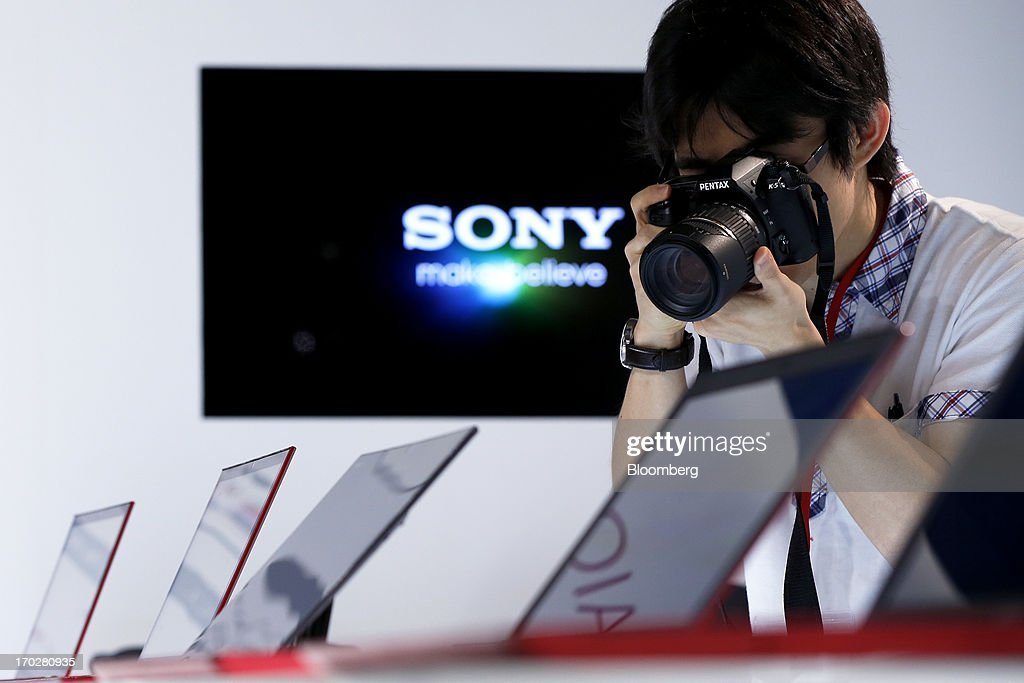 A member of the media takes a photograph with a Pentax K-5 camera of the 'red edition' Sony Corp. Vaio Ultrabook laptop computers during a product launch in Tokyo, Japan, on Monday, June 10, 2013. Sony Corp. is Japan's biggest consumer-electronics exporter. Photographer: Kiyoshi Ota/Bloomberg via Getty Images