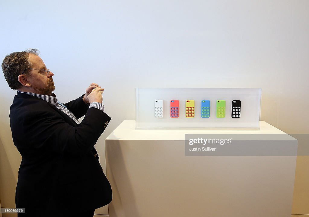 A member of the media takes a picture of a display of covers for the new iPhone 5C during an Apple product announcement at the Apple campus on September 10, 2013 in Cupertino, California. The company launched the new iPhone 5C model that will run iOS 7 is made from hard-coated polycarbonate and comes in various colors and the iPhone 5S that features fingerprint recognition security.