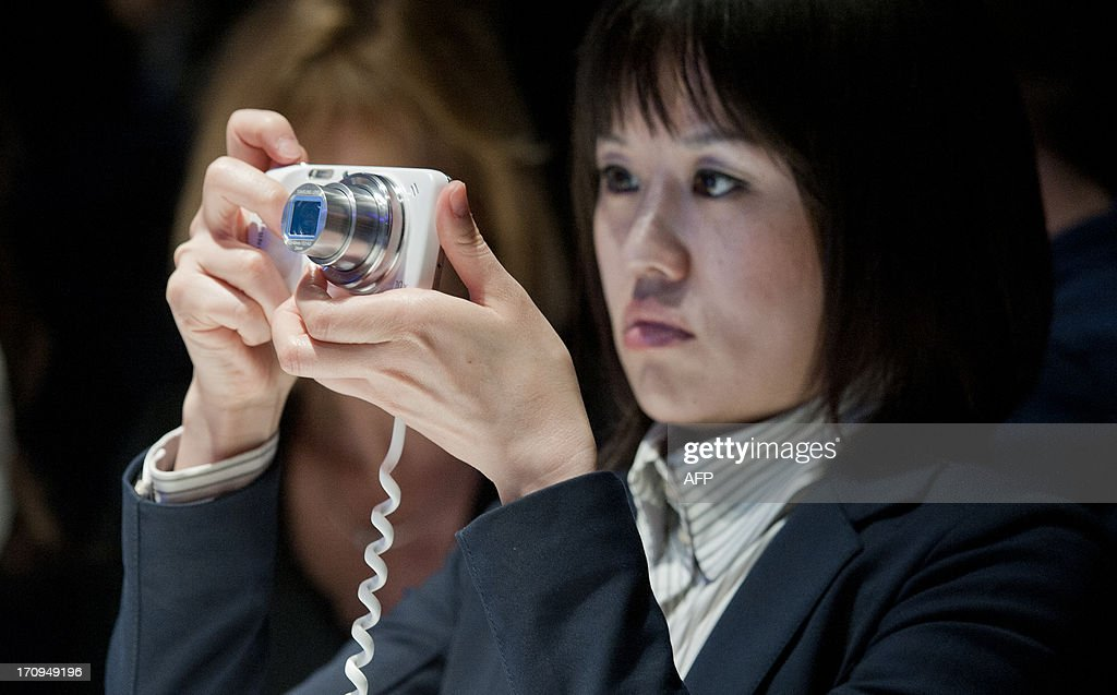 A member of the media tests the new Samsung S4 Zoom phone, a new design featuring a phone and camera combination during the world launch of new Samsung Galaxy and Ativ products at Earls Court, London on June 20, 2013.