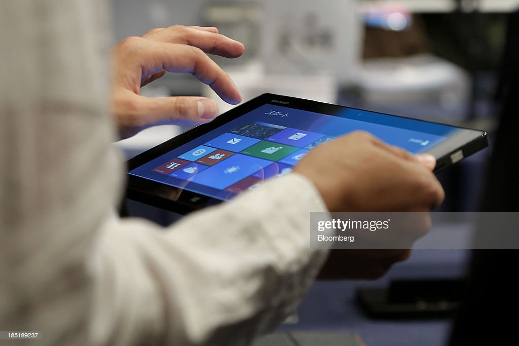 A member of the media tries out a Sharp Corp. Mebius Pad tablet, running Microsoft Corp.'s Windows 8.1 operating system, during a launch event for the operating system in Tokyo, Japan, on Friday, Oct. 18, 2013. Microsoft Chief Executive Officer Steve Ballmer, who will be retiring within a year, said the company is still working to make sure that the personal computer remains relevant as 'the device of choice.' Photographer: Kiyoshi Ota/Bloomberg via Getty Images
