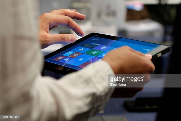 A member of the media tries out a Sharp Corp Mebius Pad tablet running Microsoft Corp's Windows 81 operating system during a launch event for the...