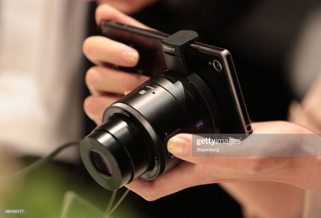A member of the media tries out a Sony Corp. Xperia Z1 smartphone mounted with a lens-style digital camera Cyber-shot DSC-QX100 after a news conference in Tokyo, Japan, on Friday, Sept. 13, 2013. Sony Corp. is betting its Xperia Z1 handset will propel it to No. 3 in the smartphone market, leaping from seventh place by vaulting past competitors such as LG Electronics Inc. and Lenovo Group Ltd. Photographer: Yuriko Nakao/Bloomberg via Getty Images
