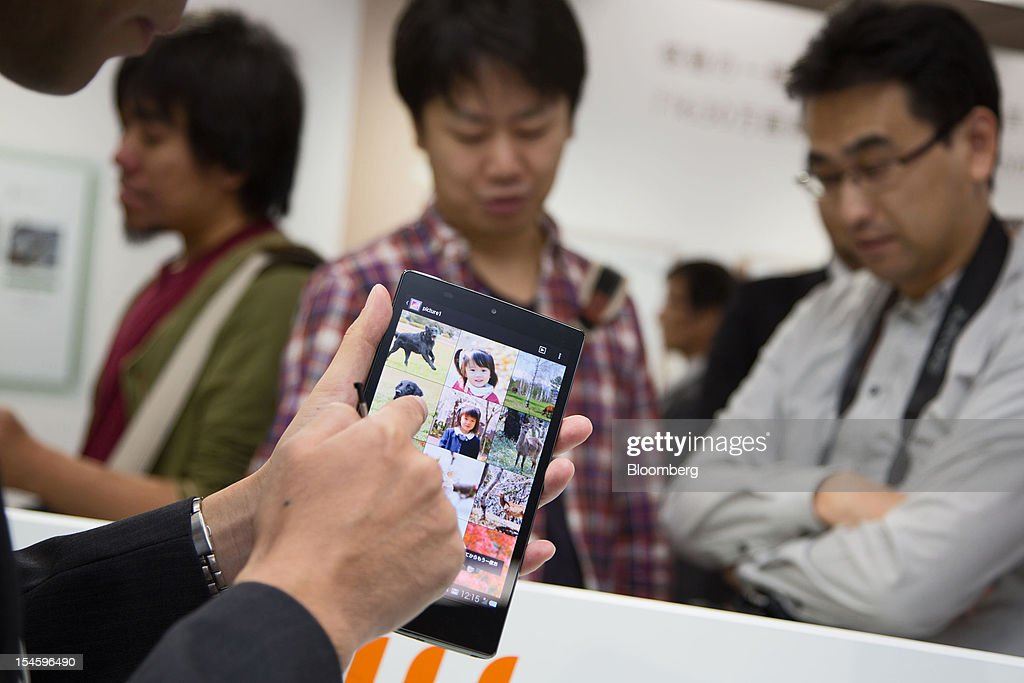 A member of the media tries out Sharp Corp.'s AQUOS Pad SHT21 tablet device that features the new IGZO display in Tokyo, Japan, on Tuesday, Oct. 23, 2012. Sharp began making smartphone displays using a semiconductor technology known as IGZO this month at its plant in Tenri, central Japan, according to a company spokesman. Photographer: Noriyuki Aida/Bloomberg via Getty Images