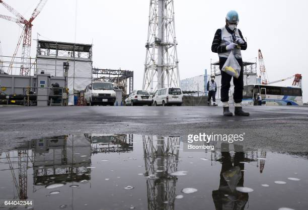 A member of the media uses a geiger counter during a tour of Tokyo Electric Power Co's Fukushima Daiichi nuclear power plant in Okuma Fukushima Japan...