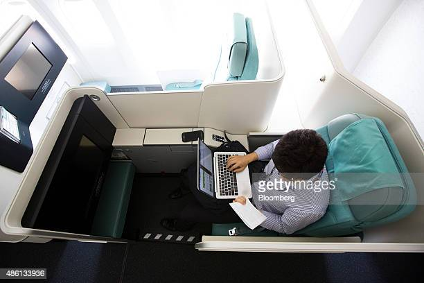 A member of the media uses his laptop computer inside a business class seat of a Korean Air Lines Co Boeing Co 7478 passenger aircraft during a media...