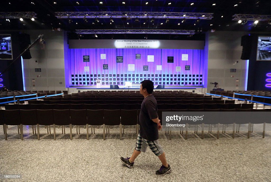 A member of the media walks through the plenary hall at the Dalian International Conference Center in Dalian, China, on Tuesday, Sept. 10, 2013. The World Economic Forum Annual Meeting Of The New Champions 2013 will be held in Dalian from Sept. 11 to 13. Photographer: Tomohiro Ohsumi/Bloomberg via Getty Images