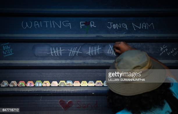 TOPSHOT A member of the media writes on a wall opposite the forensics wing of the Hospital Kuala Lumpur where the body of Kim JongNam the halfbrother...