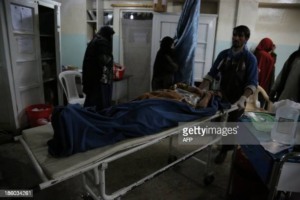 A member of the medical staff carries a victim of a roadside bomb at a hospital in the Andar district of the Ghazni province on October 27 2013 A...