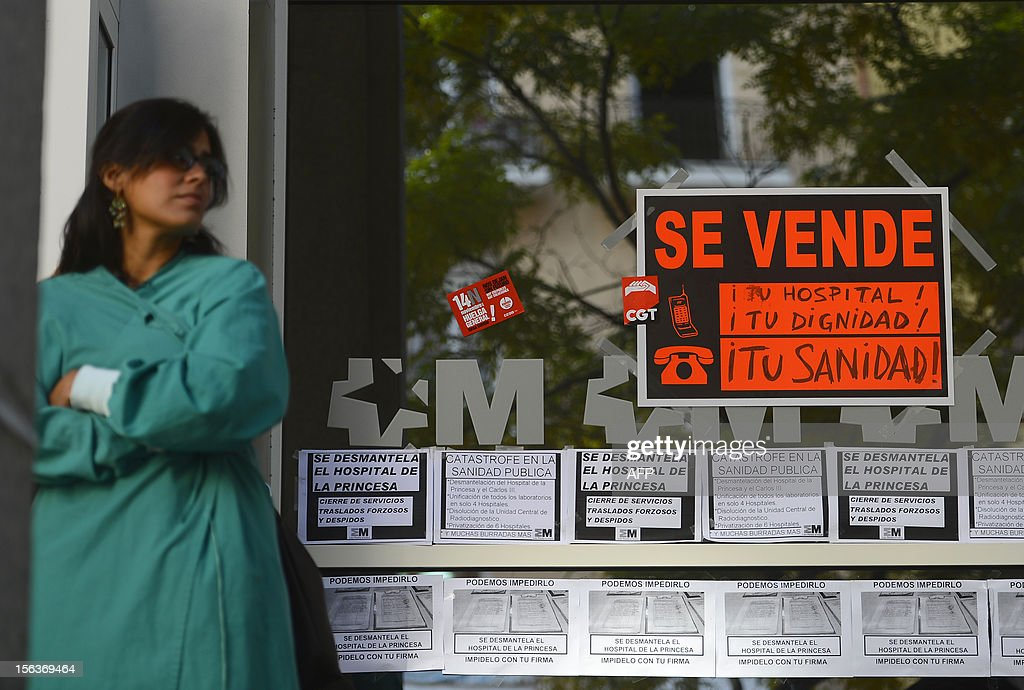 A member of the medical staff stands next to a placard reading 'Your hospital, your dignity, you health, On sale' at the entrance of the Princesa Hospital during a general strike on November 14, 2012 in Madrid. General strikes in Spain and Portugal will spearhead the day of action called by European unions and joined by activists as anger over governments' tight-fisted policies boils over.